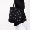 Black tote bag with all-over moon print on woman's arm.