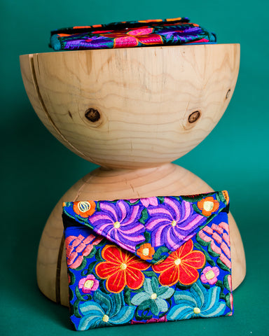 colorful embroidered clutch on wooden stand