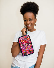 woman holding pink clutch bag and smiling