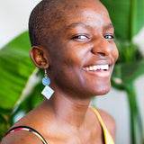 black woman smiling with blue leather earring