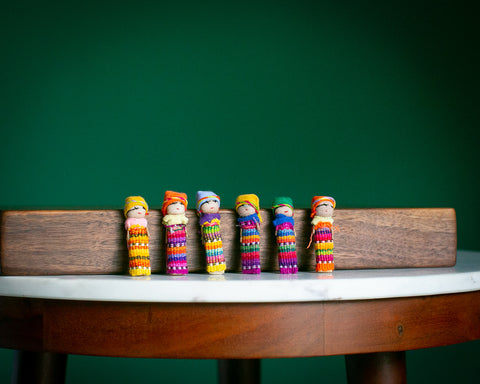 worry doll family on a table lined up in a row