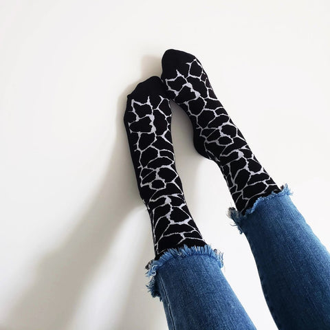 giraffe socks on white wall