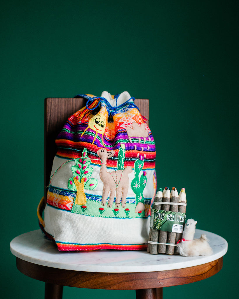 backpack with embroidery patterns and wooden crayons on table