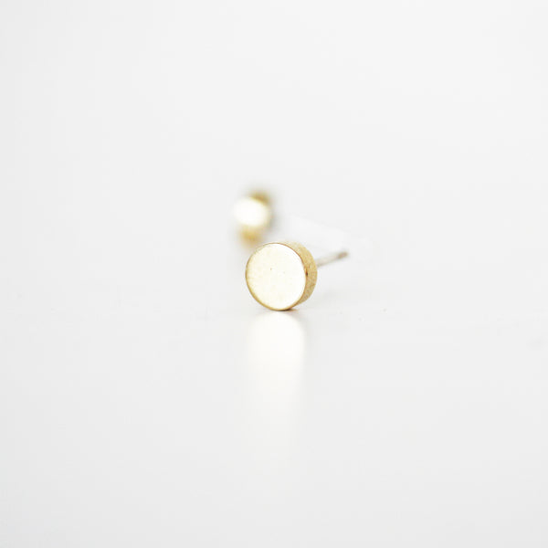 A pair of beautiful minimalist circle earrings in polished brass, with sterling silver posts.