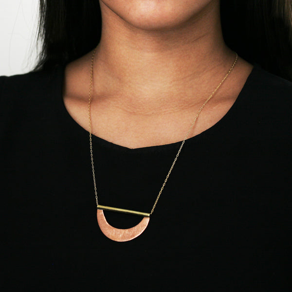 A woman wearing a stylish brass and copper necklace over a black shirt.