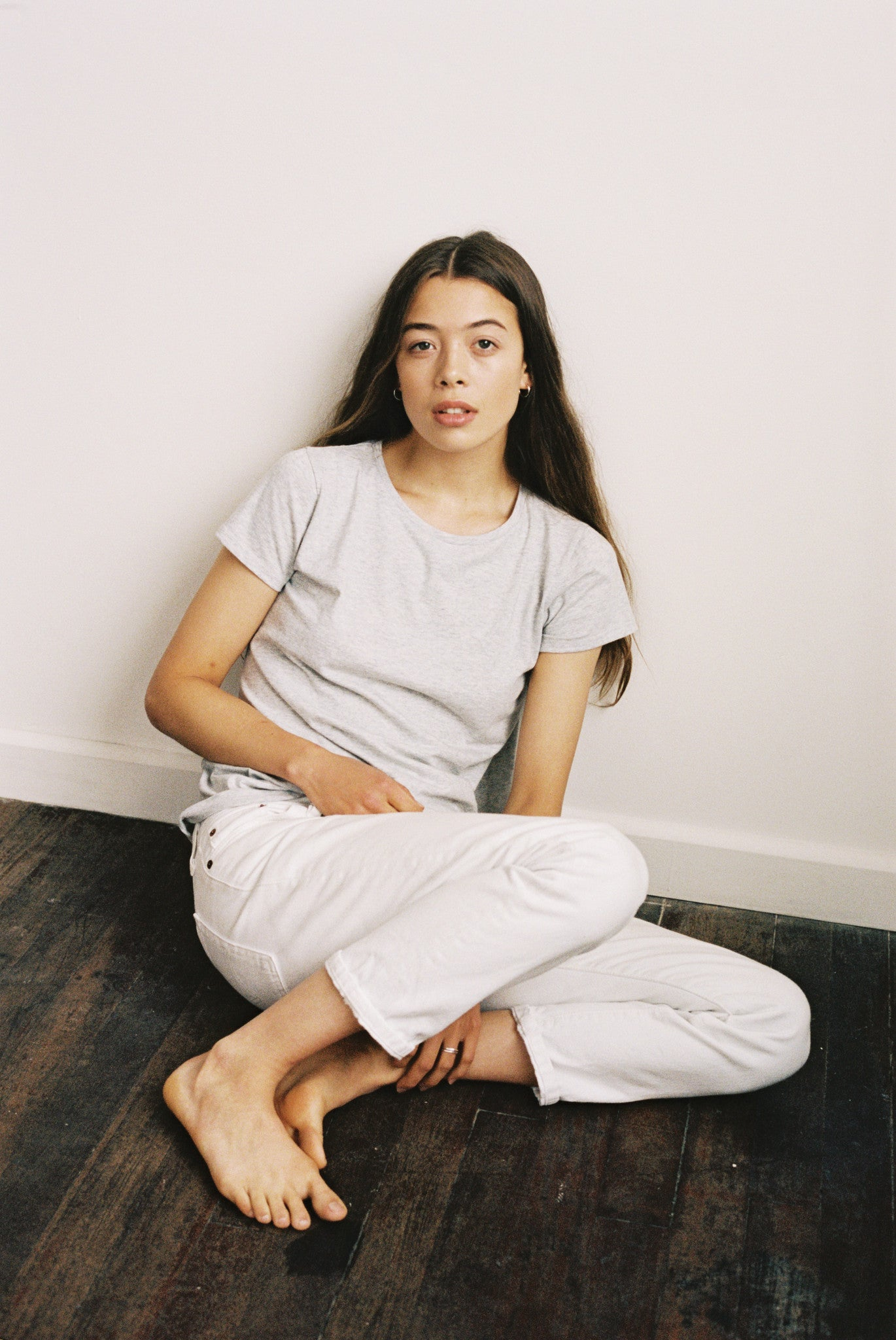 Woman sitting on the floor in her organic grey cotton high neck t-shirt.
