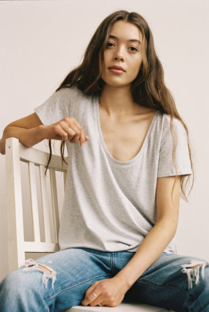Woman sitting on chair in grey organic cotton scoop neck t-shirt.