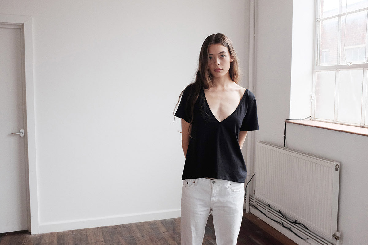 Woman posing in black v neck sustainable t-shirt.