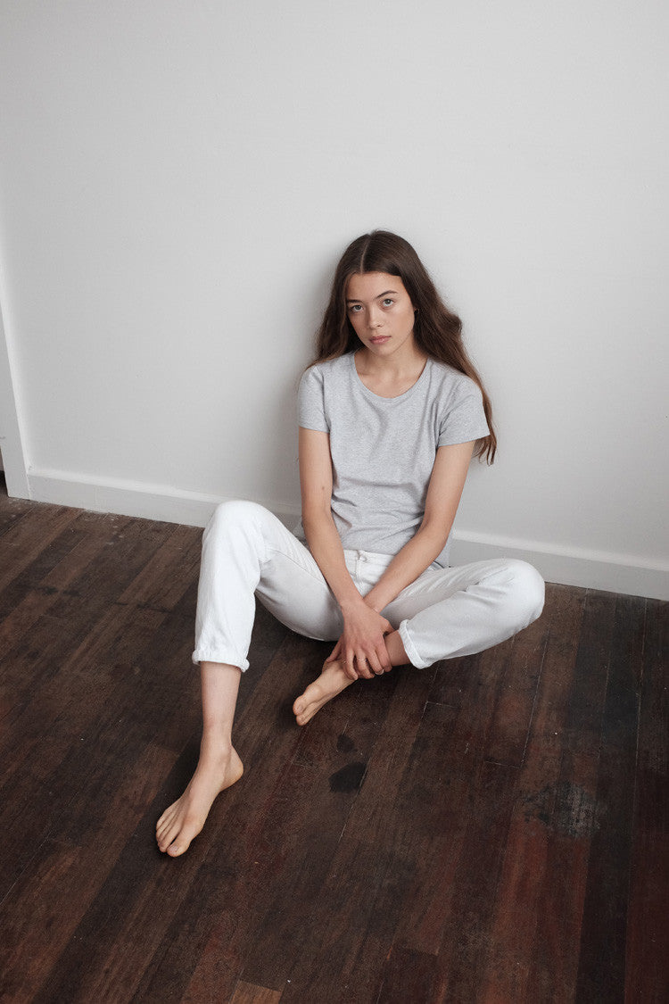 Woman wearing a grey high neck organic cotton t-shirt sitting on the wooden floor.
