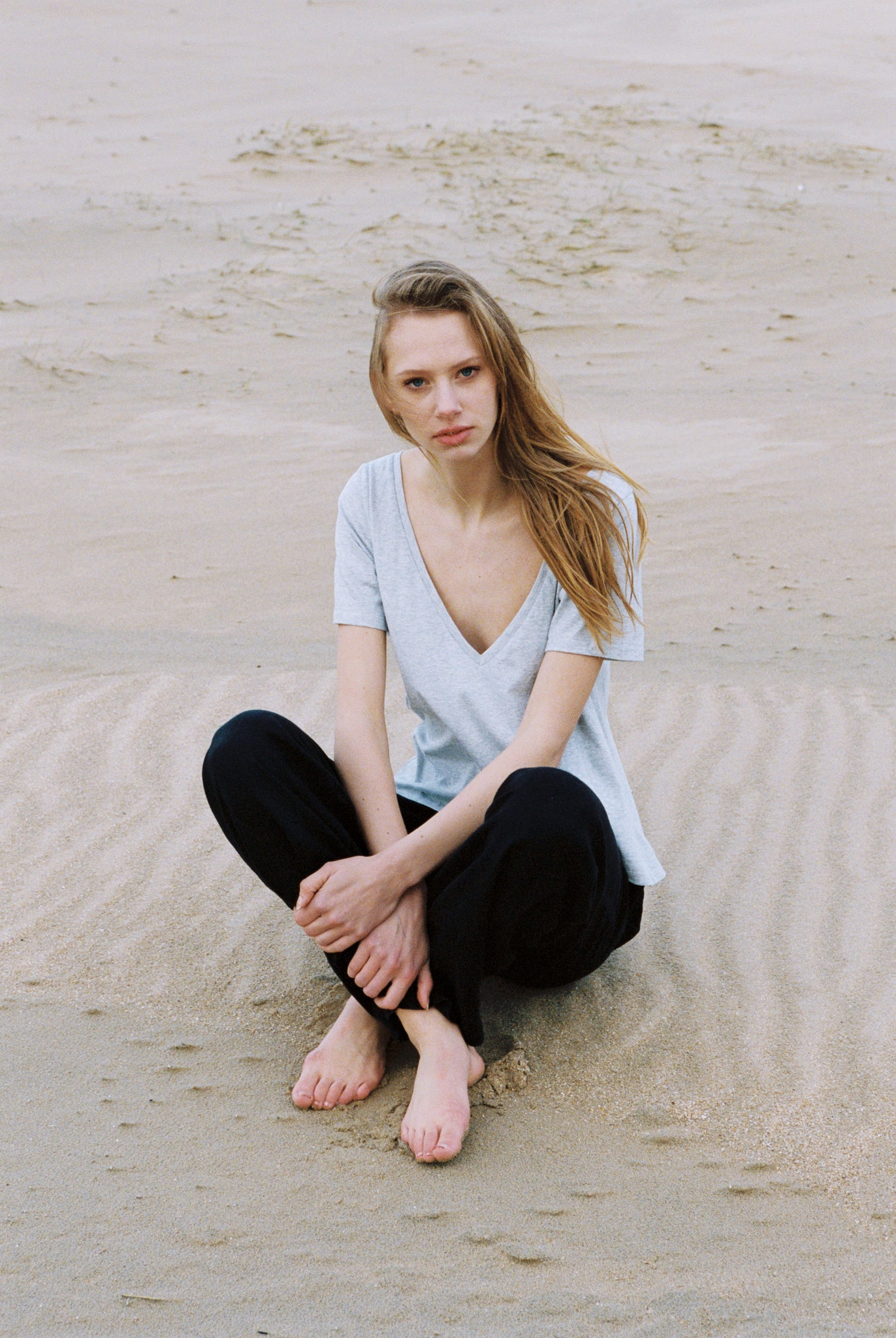 Woman sitting on beach with her organic grey cotton v neck t-shirt on.