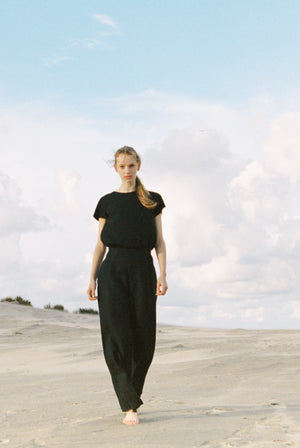Woman in sustainable high neck black t-shirt walking on the beach.