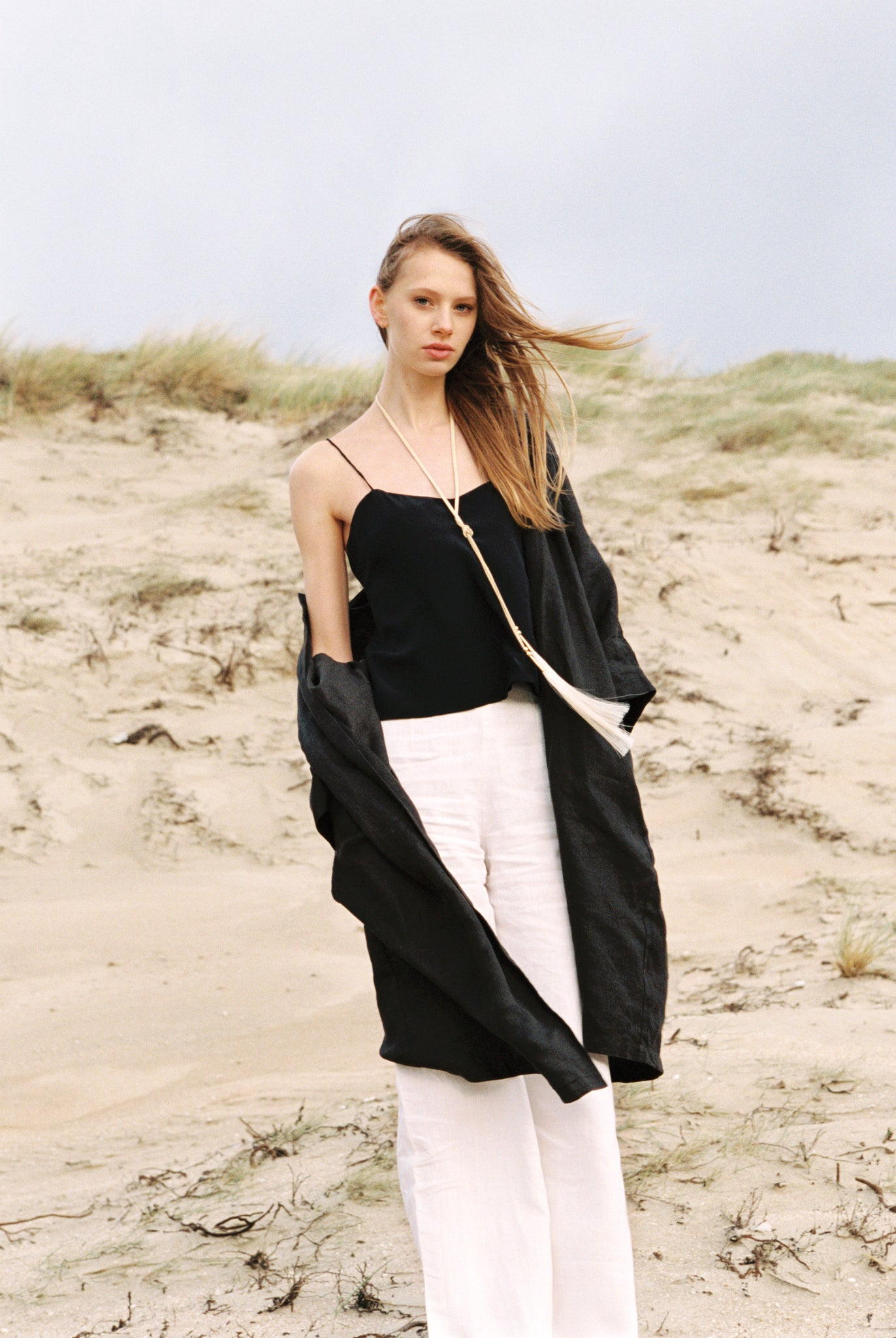 Woman on beach wearing her organic silk camisole.