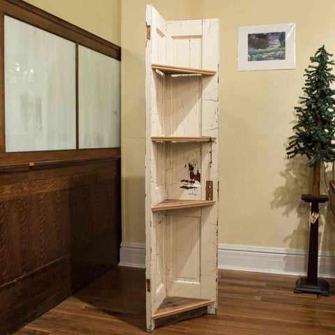 Rustic handcrafted corner shelf made of a reclaimed old farmhouse door. Created by Born Again Building and sold exclusively at Chestnut Studios, Lindsborg, KS