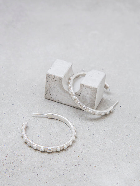 sculptural dotted texture sterling silver hoop earrings on concrete soft gold co