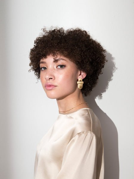 gorgeous naturally curly glossier inspired makeup statement shapes earrings in gold on gabby lookbook for soft gold co by dianna gendron
