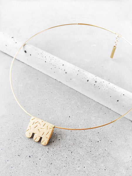 post modern jewelry design gold pendant choker on cement memphis style
