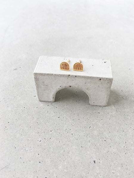soft gold co benchmark stud earrings on concrete arch