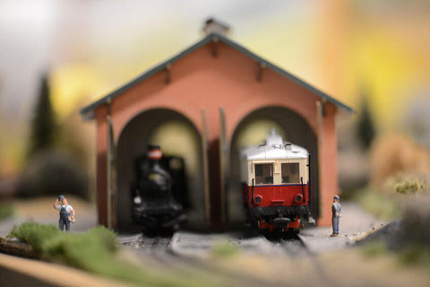 A model train prepares to leave the station while model conductors accompany it
