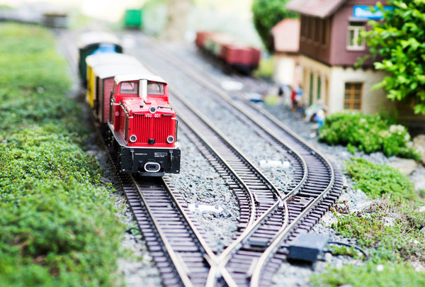 Model train layout with red engine car on the tracks