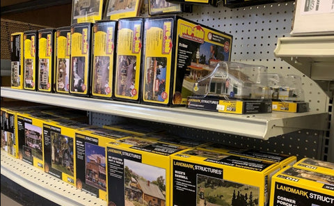 HO Scale trains and buildings lined up on a store shelf.