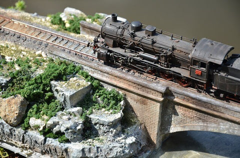 A diorama of a weathered model steam train crosses a bridge toward a rocky outcrop full of fake vegetation