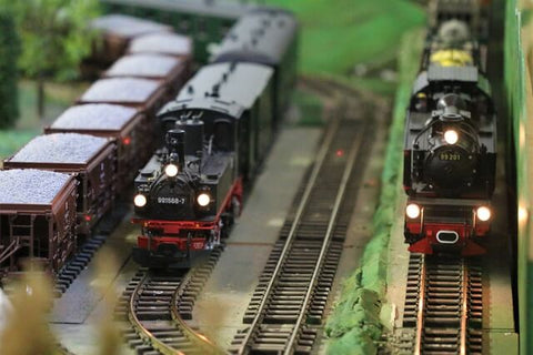 Black and red steam locomotive models sit at rest next to each other at a station