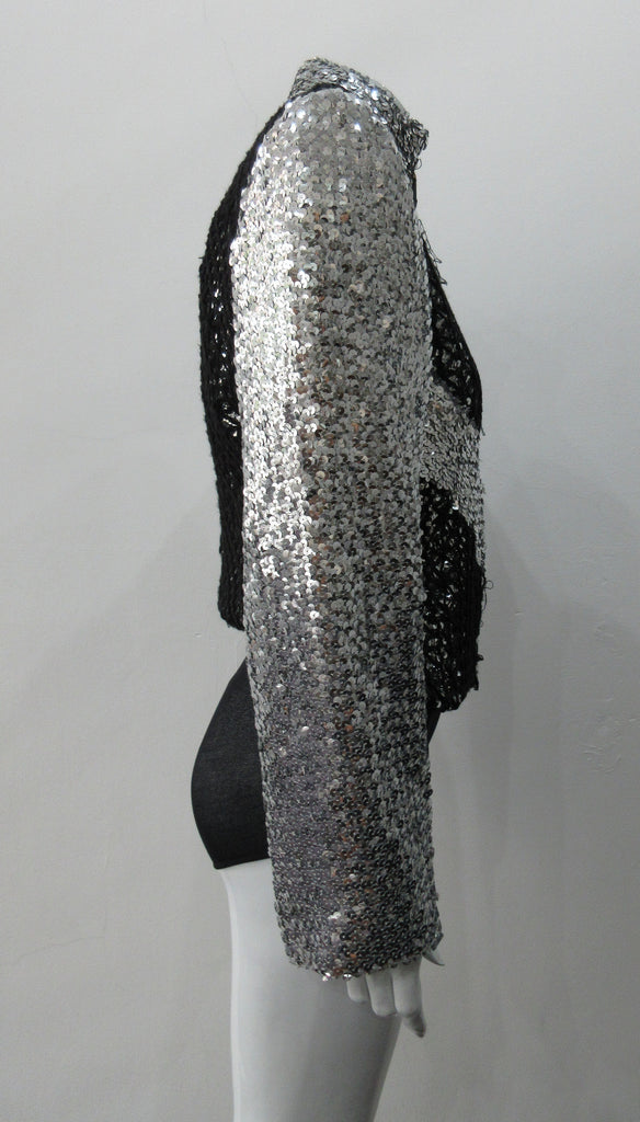 Silver Glitter Jacket with Black Crochet. Full on glittered siver colour sequin jacket with partblack crochet covered for a sporty feel. Crochet detailing unravelling/fraying in areas as done for intentional effect. CF zipper with 8.5cm high collar.  CB length 52cm. Sleeve length from side neck point 76cm. 950g approximate weight. 90% Polyester, 5% Elastine, 5% Metallic Contrast: 100% Cotton. Lining: 100% Polyester. Dry Clean Only. Made in England