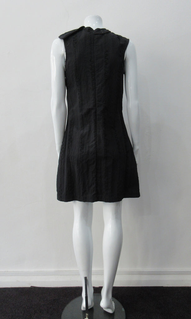 Black Flap Shoulder Dress. The ideal little black sleevelss dress featuring assymetric styling with piping. CB invisible zipper. Fully lined. Size 8