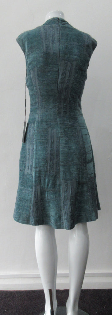 Round Seam Dress. Dark sea green textured dress with curved neck panels. With CB zipper. CB length 93cm. 82% Wool, 18% Nylon. Lining: 100% Rayon. Dry Clean Only, Made in Croatia