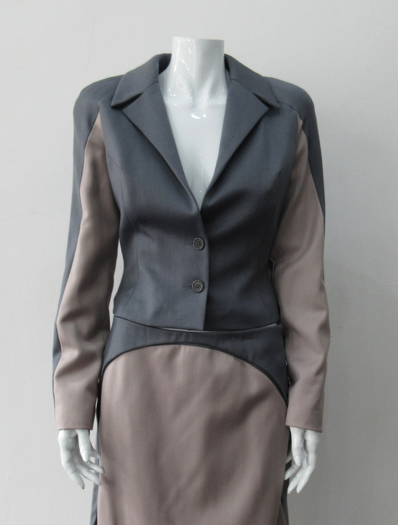 Cropped Point Sleeve Jacket. Pointed peak collared cropped style in grey with light taupe/rose contrast sleeve panels. Relaxed fit with soft raglan sleeves. Shown with matching skirt. Size 8. 100% Wool. Lining: 100% Rayon, Dry Clean Only. Made in England