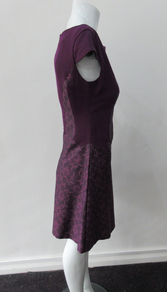 Pointed Tip Dress. Rich purple wool dress with matching floral book print contrast panels and base. Soft cap sleeve top and CB zipper. CB Length 82cm. 550g approximate weight. 100% Wool. Contrast: 100% Cotton, Lining: 100% Rayon. Dry Clean Only, Made in England