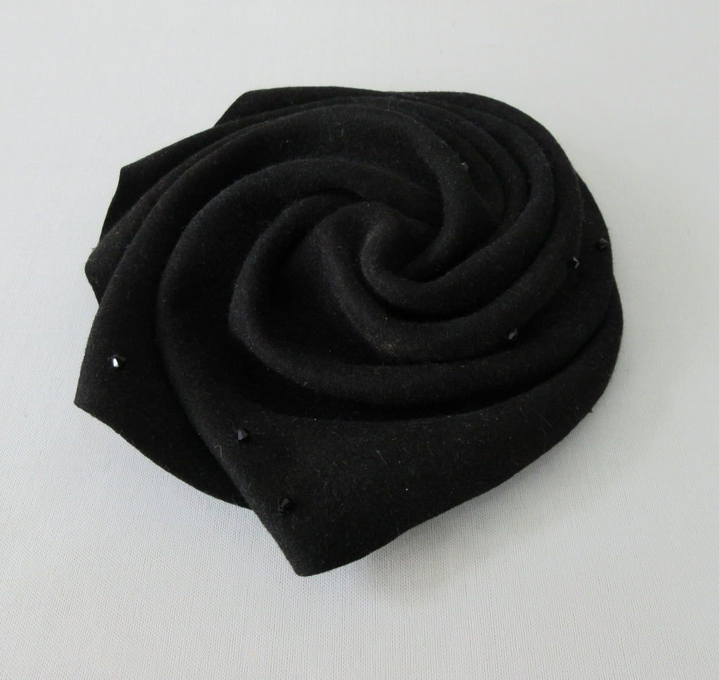 Olka Hats Black Felt Twirled Mini Black Felt Twirled with Black Rinestones, and elastic for chin. Retro style can be worn on top or side of head. 20cm x 21cm inside diameter. 30g approximate weight. Made in Canada
