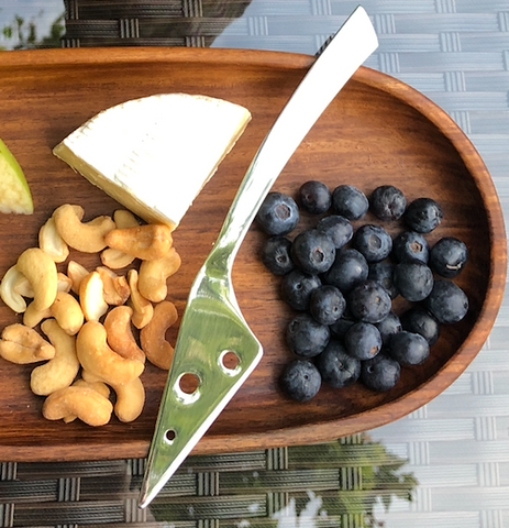 cheese knife on wooden tray with fruit for do good shop subscription box ethical gifts