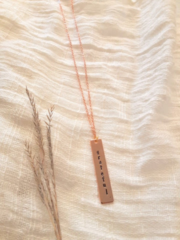 grateful.rose.gold.vertical.bar.necklace.handmade.by.women.survivors.sold.at.do.good.shop.ethical.gifts.jewelry.for.her.mom.holiday.anniversary