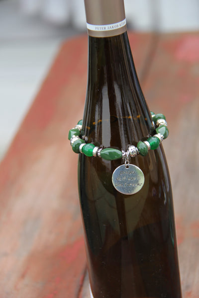"Green beads bottle bracelet with ""Dream as if you'll live for ever"" charm."
