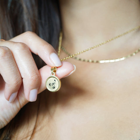 The zodiac disc pendant is an 18k gold design displaying either a unique script or star sign symbol.