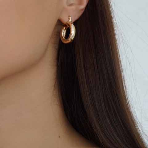 Our thick hoop huggie earrings with an 18k gold plated base are the perfect choice for an everyday accessory.