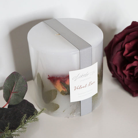 Red rose pillar candle featuring dried velvet roses and rich geranium blooms with a floral scent.