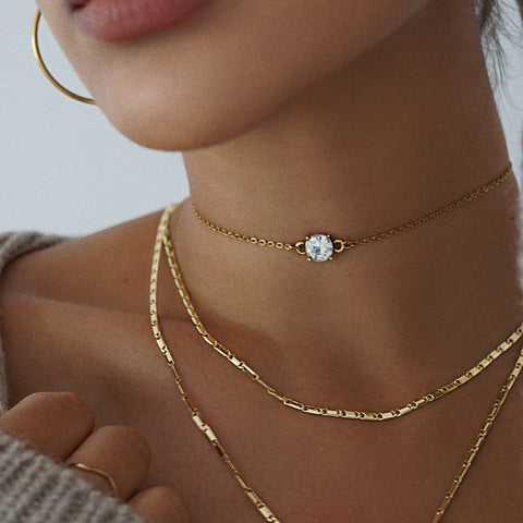 Layer up with our statement rhinestone choker and our gold plated chain necklace for a day to night look.