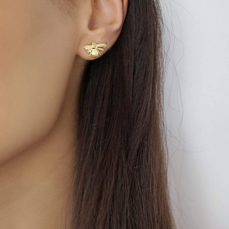 Model wearing Nikita By Niki BELLA bumble bee stud earrings in gold
