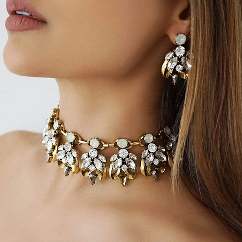 The LEILANI statement earrings and choker set with a rhinestone encrusted design and antique plated metal base. A beautiful dangling ear accessory to wear matching together or separately.