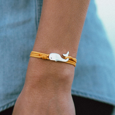 Woman wearing Cape Clasp silver whale bracelet with yellow cord