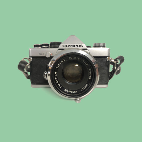 Olympus OM2 with a 50mm lens, including a vintage metal lens hood & original leather case.