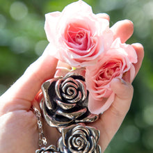 Load image into Gallery viewer, Large stainless steel rose pendant on our stainless steel infinity chain  next to our medium pendant set by pink roses. This pendant will not tarnish or dent. Lovely rose flower pendant. The rose flowers are being held by a woman's hand.
