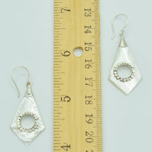 Load image into Gallery viewer, Abalone or Mother of Pearl Sterling Silver Earrings. Geometric diamond shape. Silver work. one and a quarter inch long. Pierced earrings. Fish hook There is a whole cut out in the center with silver scalloped around the edge of the whole.