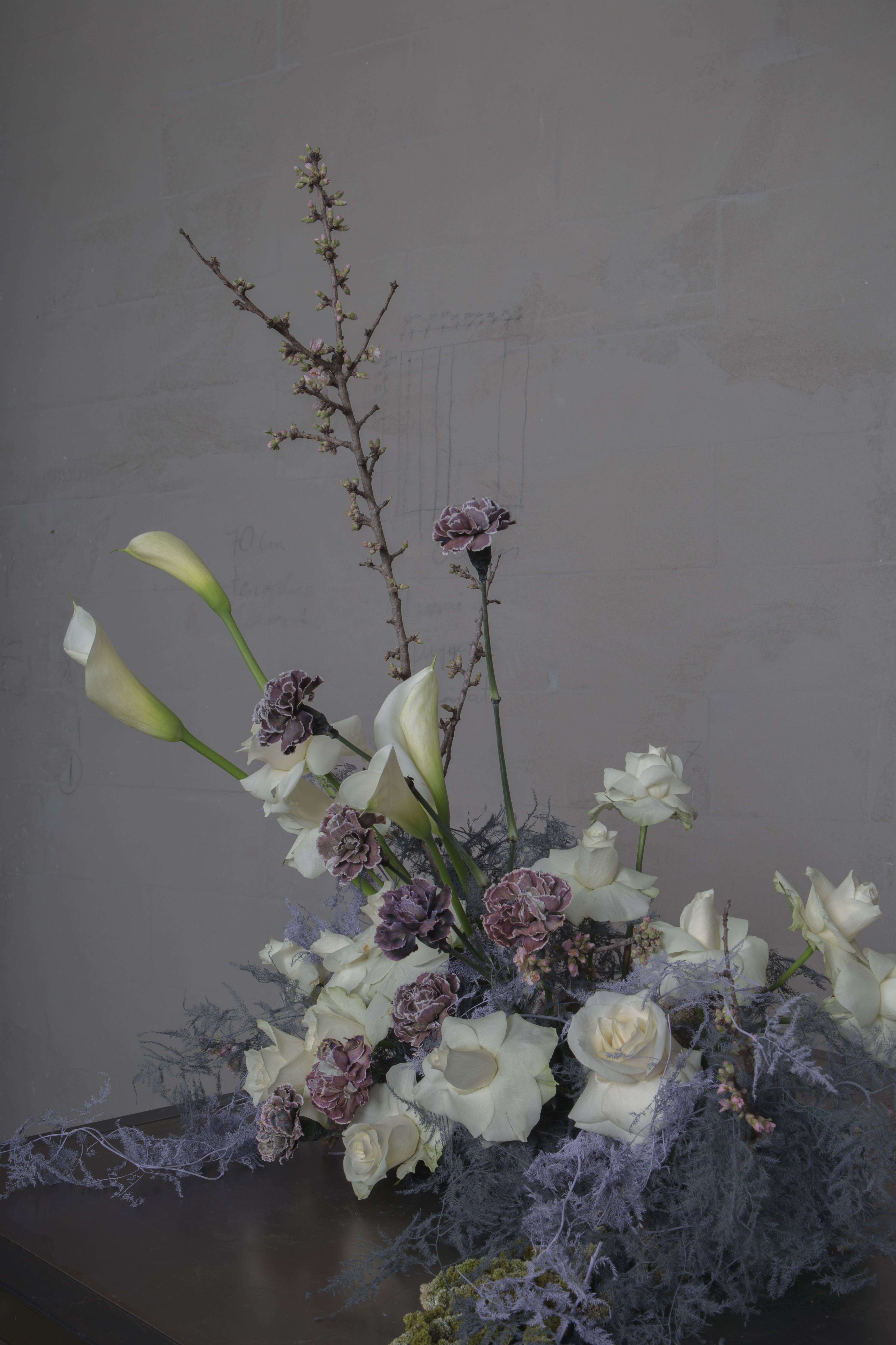 Table-piece-Finecut-weddings-collection-8-2019-lilac-and-white-with-fully-bloomed-roses-callas-lilac-dyed-asparagus-fern-and-striped-carnation-with-amaranth-tails-and-branches-of-almond