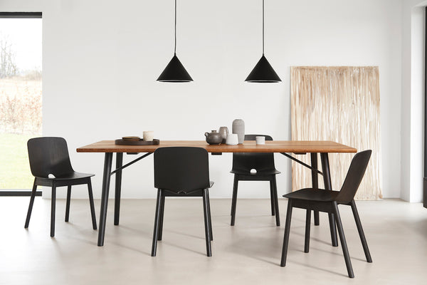 Capricho, Annular Pendant Light in Black styled over dining table with Black Mono Dining Chairs, WOUD Design