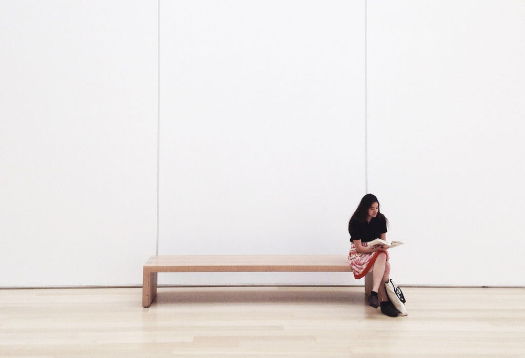 Woman sitting alone at an art gallery reading by herself