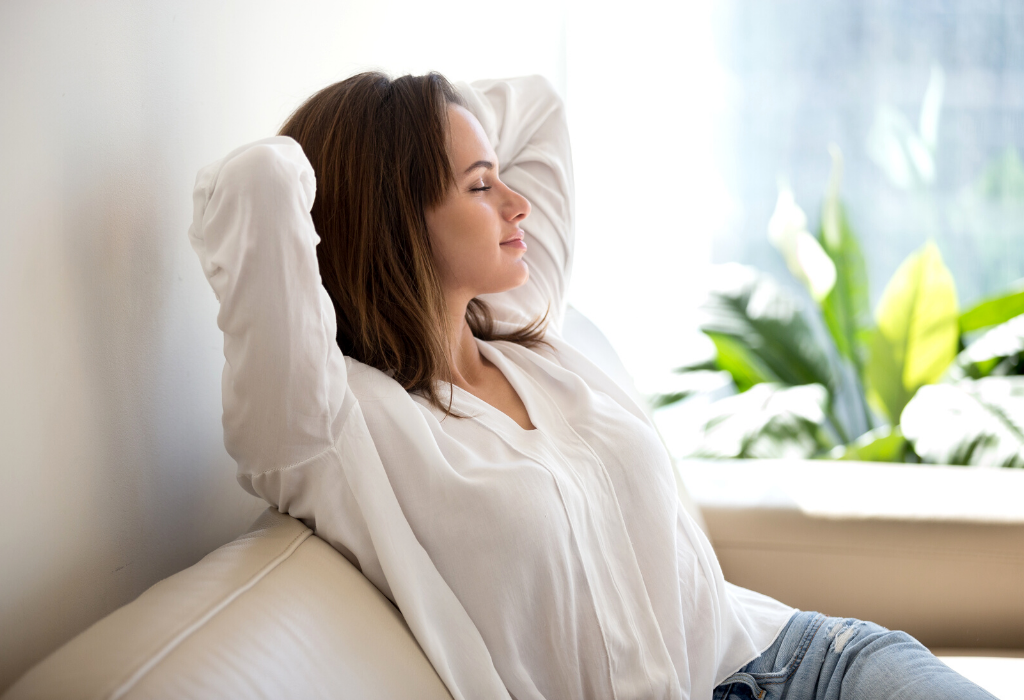 A woman on her couch with her hands behind her head relaxing