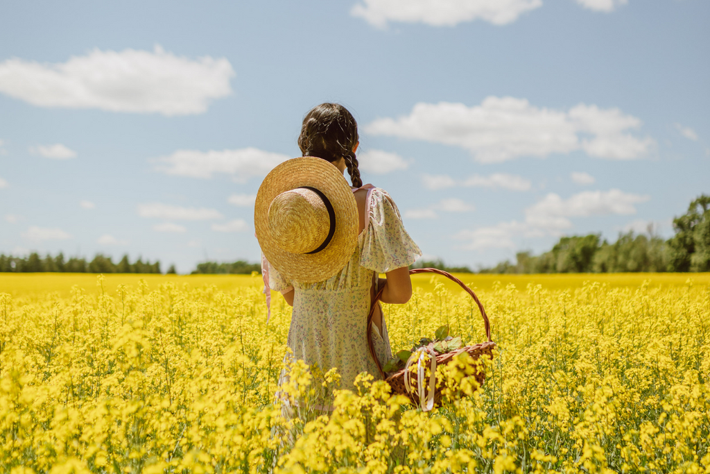 Woman standing in the middle of a field of flowers